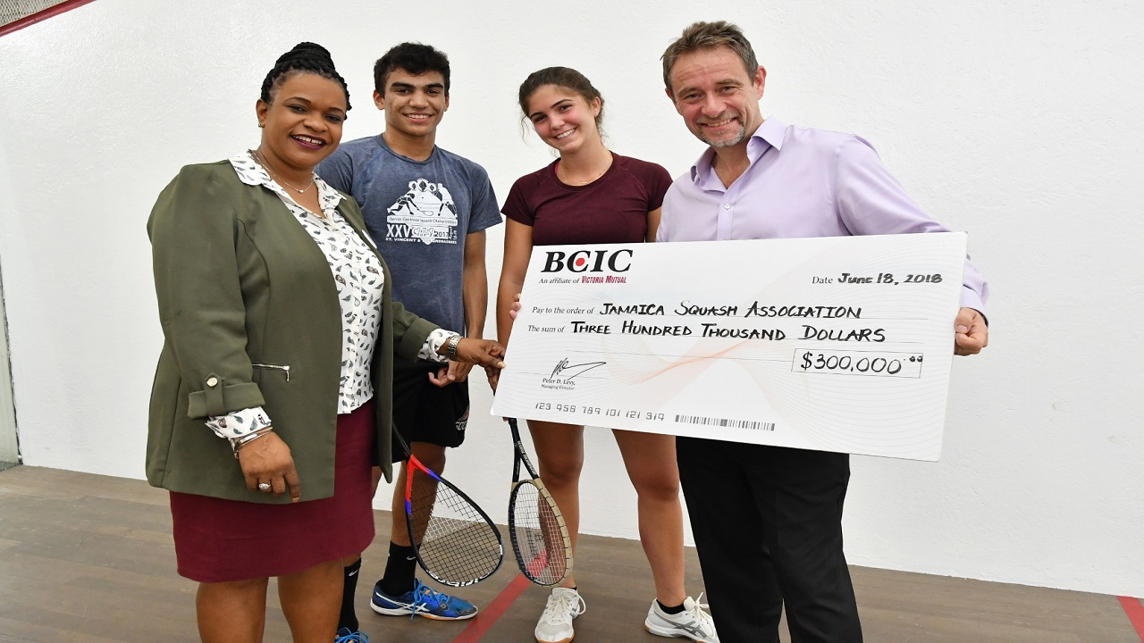 Chris Hind, (right) President of the Jamaica Squash Association (JSA), shows off the $300,000 sponsorship cheque, which he received from Michelle Anderson, (left) General Manager, Sales and Distribution at BCIC for the staging of the 2018 All Jamaica Junior Squash Championships.  Sharing in the moment are Jonathan Walker, (second left), a strong contender for the Boys' Under 19 title and reigning All Jamaica Girls' Under-17 champion, Mia Mahfood.