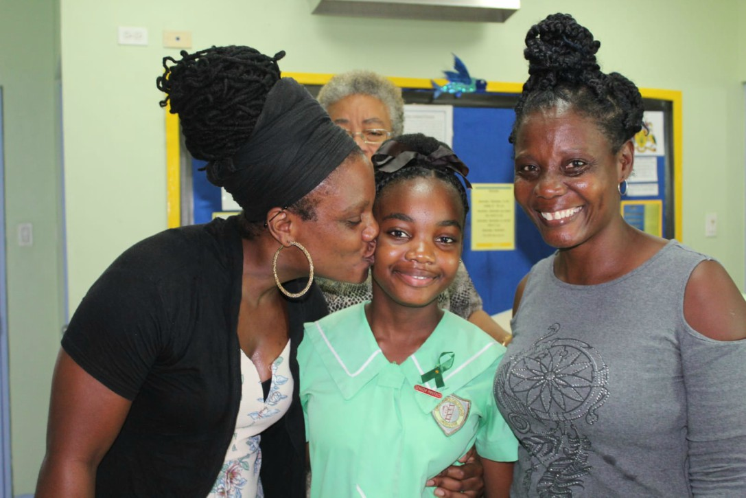 Zahzara Barrow (center) receives a kiss from mummy Shari Greenidge (left)  as grandmum Natalie Millar (right) looks on.