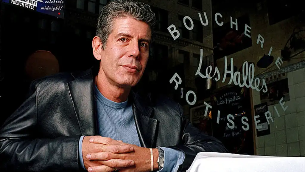 FILE - This Dec. 19, 2001 file photo shows Anthony Bourdain, the owner and chef of Les Halles restaurant, sitting at one of the tables in New York. (AP Photo/Jim Cooper,File)