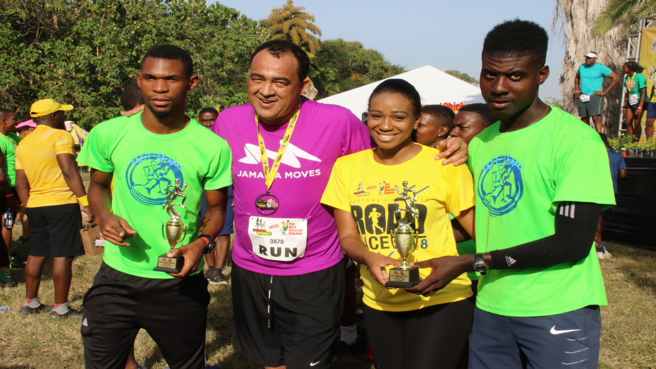 UCT Steppas' Garfield Gordon (left) and Oshane Archibald (right), overall winners in the 5k and 10k respectively, pose with their trophies alongside Health Minister Dr Christopher Tufton and Best Dressed Regional Marketing Programmes Manager, Avadaugn Sinclair. (PHOTOS: Llewellyn Wynter)