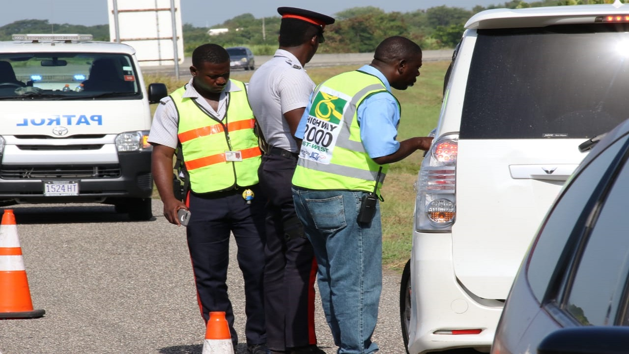 Police officers and a Trans-Jamaican Highway worker look at a vehicle that overturned along the PJ Patterson Highway on Monday morning. (PHOTOS: Llewellyn Wynter)