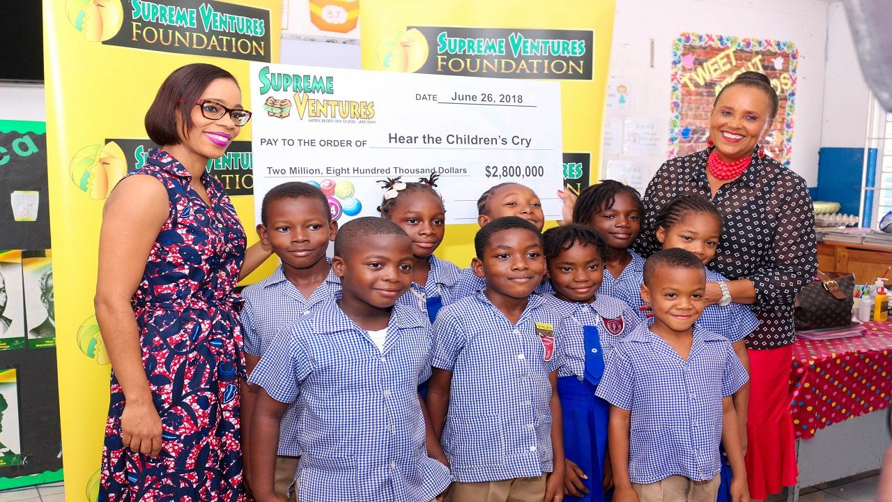 SVL Assistant Vice President, Simone Clarke-Cooper presents Founder/Director of Hear the Children's Cry with a cheque of $4.2 million, signalling the beginning of a partnership to establish Hear the Children's Cry's Missing Children's Family & Community Social Work Programme. The presentation was made June 26 at Swallowfield Primary, White Hall Avenue, Kingston.