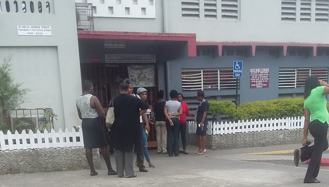 Parents gather in front of the Half Way Tree Primary School in St Andrew on Thursday morning as they await GSAT their children's results. (PHOTO: Kimmo Matthews)