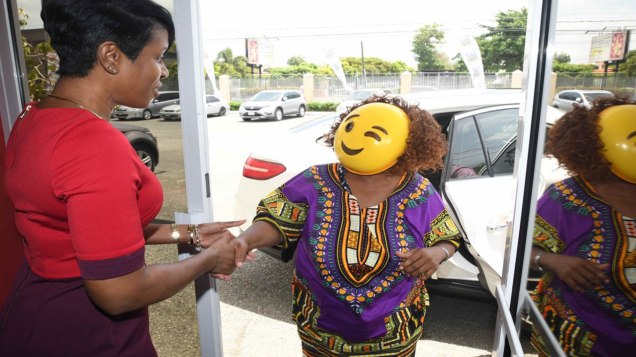 Ann-Dawn Young-Sang (left), President and CEO of Supreme Ventures greets N. Gray, the Super Lotto Jackpot winner.