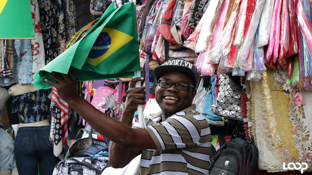 This vendor is all smiles as he displays Brazilian flags, which are among the hottest items as World Cup fever hits Jamaicans. (PHOTOS: Ramon Lindsay)