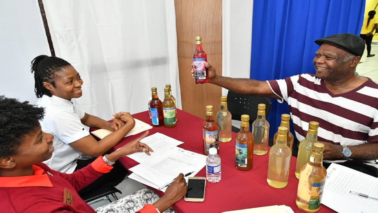 Tropical Wines Proprietor, Winston Butler showcases his fruit-flavoured wines to judges Simone Harris (left), Tourism Networks Analyst at the Tourism Enhancement Fund (TEF) and Jamaica Promotions Corporation's (JAMPRO), Marcia Evans.