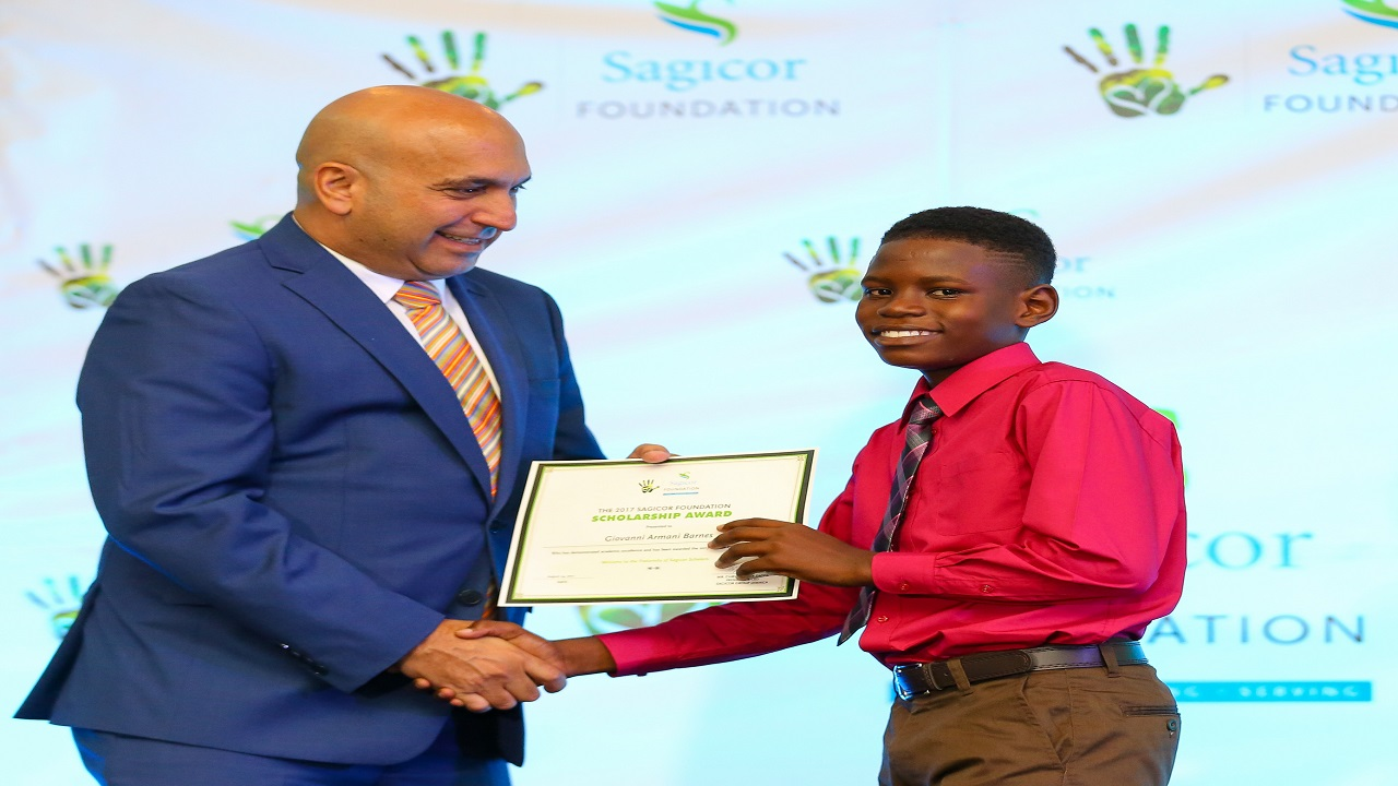 Sagicor Group Jamaica President Christopher Zacca presenting Giovanni Barnes with grant towards his education last year.