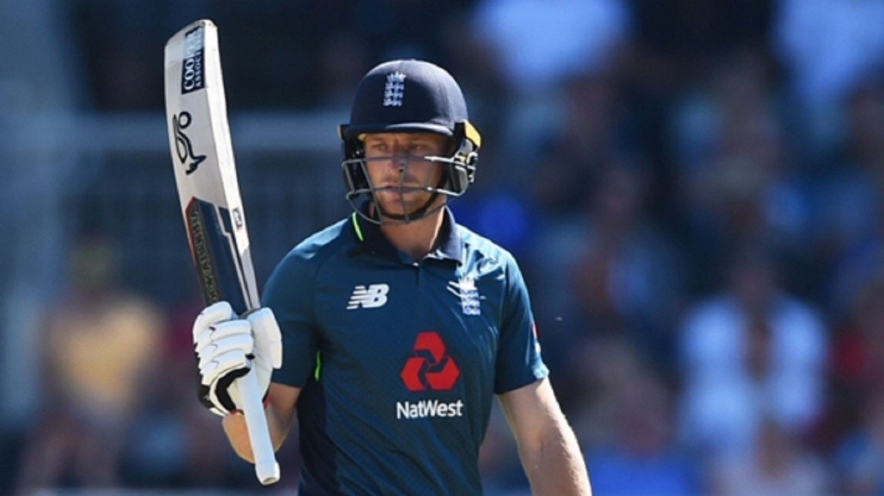 Jos Buttler raises his bat after reaching his half-century.