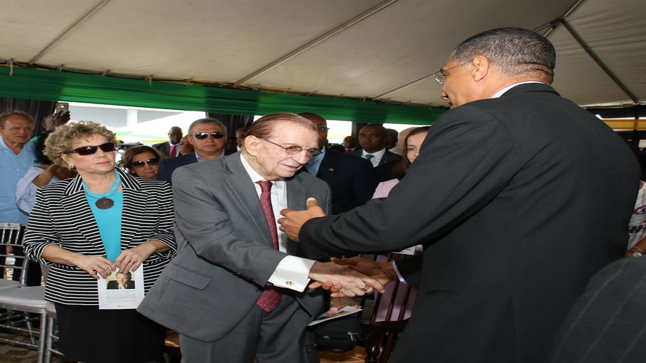 Prime Minister Andrew Holness (back partially turned, right) greets former Prime Minister Edward Seaga (centre), who the North-South Highway is being named after. Looking on is Seaga's wife, Carla Seaga (left). (Photos: Llewellyn Wynter)