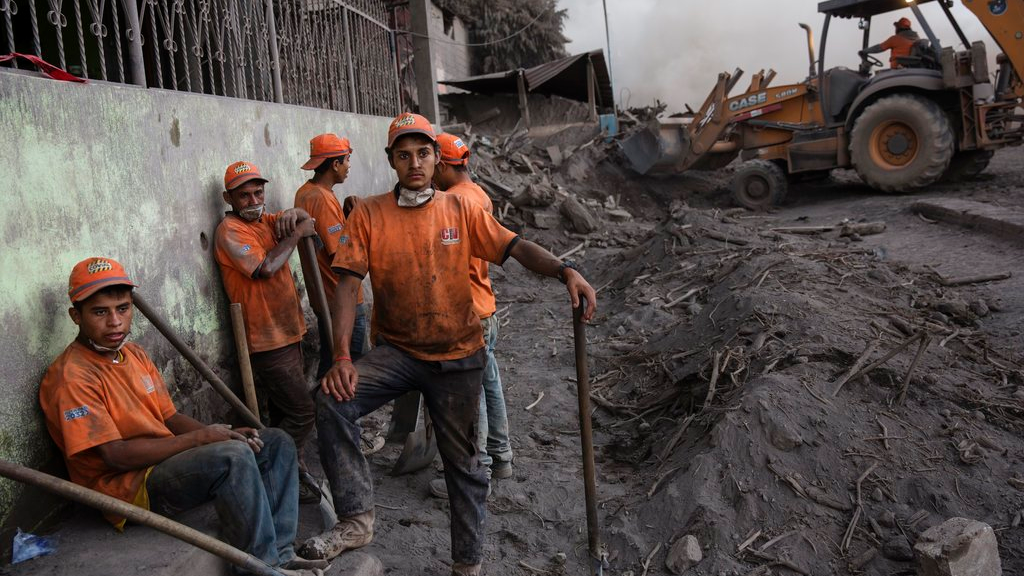 """Rescue workers gather in the disaster zone covered in volcanic ash near the Volcan de Fuego, or """"Volcano of Fire, in the El Rodeo hamlet of Escuintla, Guatemala, Wednesday, June 6, 2018. Firefighters said the chance of finding anyone alive amid the still-steaming terrain was practically nonexistent 72 hours after Sunday's volcanic explosion. (AP Photo/Rodrigo Abd)"""