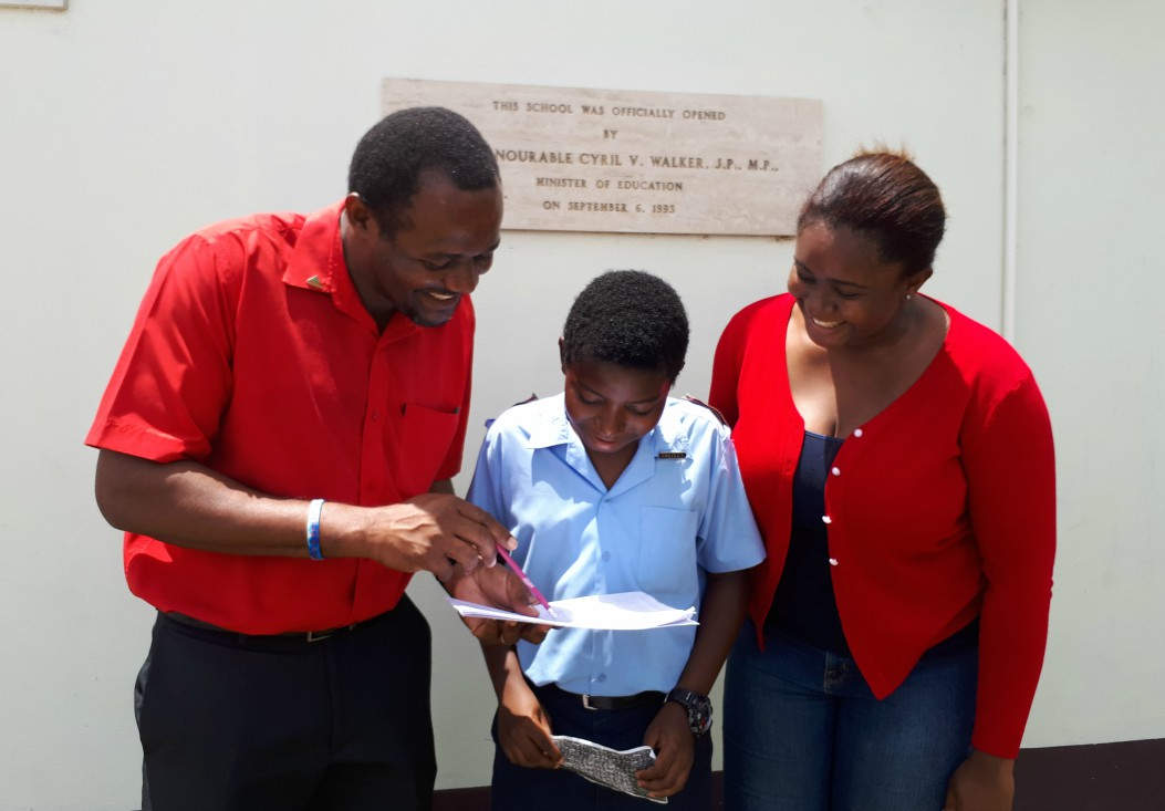 (left) Teacher Terry Carrington reviewing St. Stephen's Primary Common Entrance results while student Amaani Holder and his sister Adrienne Holder look on.