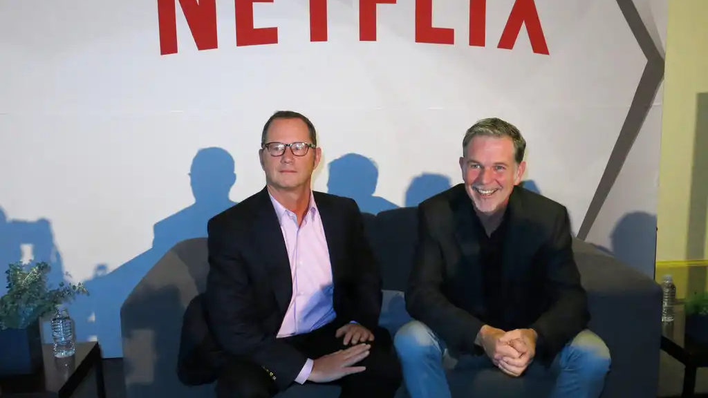 FILE - In this Nov. 24, 2014 file photo, Reed Hastings, CEO and founder of Netflix, right, sits with Jonathan Friedland, global director of communications, as they pose for a portrait during a press conference about their three years of doing business in Latin America, in Mexico City. (AP Photo/Berenice Bautista, File)