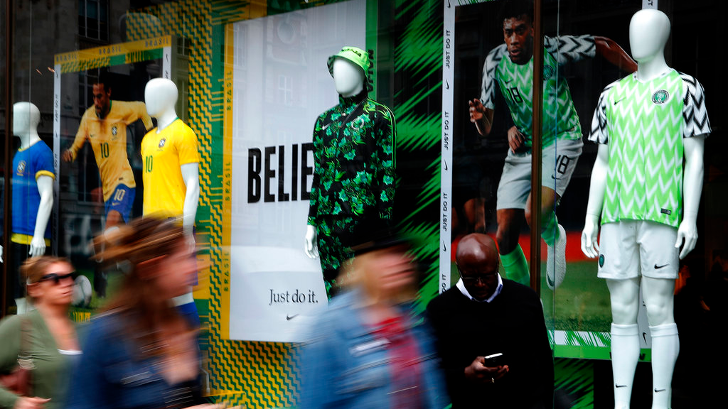 In this June 5, 2018 photo people walk by Nigerian and Brazil national soccer team jerseys which are on display at a shop in London. (AP Photo/Frank Augstein)