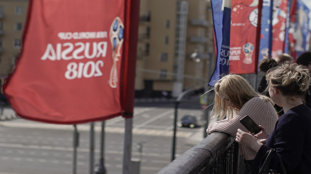 Women look over from the Krymsky Bridge, adorned with banners of the 2018 football World Cup, in Moscow, Russia, Wednesday, June 13. A senior Russian lawmaker advised Russian women Wednesday to be vigilant during any romantic encounters with foreign fans flocking to Russia for the World Cup so as not to end up raising their children alone.