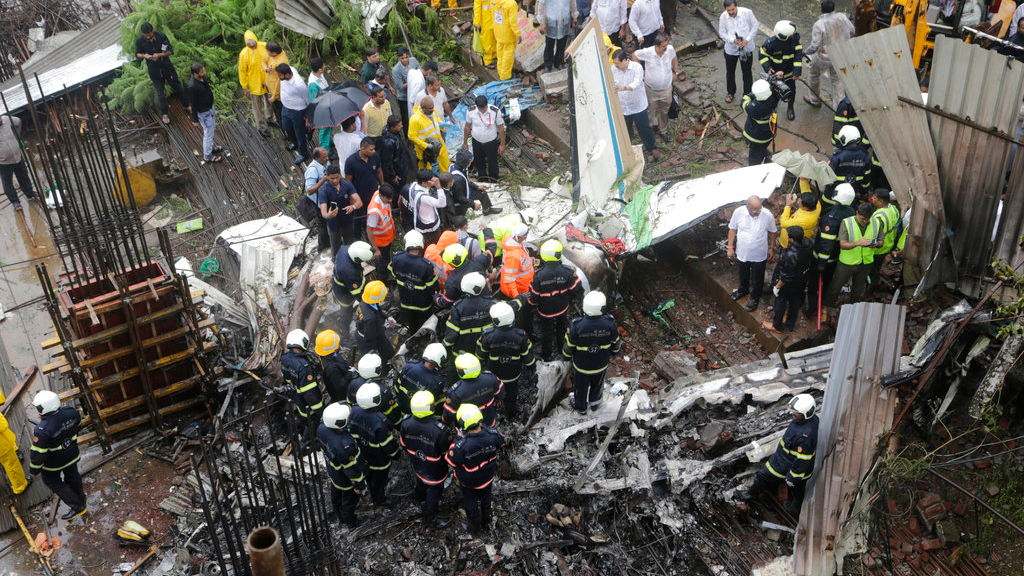 Rescuers stand amid the wreckage of a private chartered plane that crashed in Ghatkopar area, Mumbai, India, Thursday, June 28, 2018. An official said it was not immediately known how many people were on board the aircraft. Five bodies were recovered from the wreckage and rescue work was continuing. (AP Photo/Rajanish Kakade)
