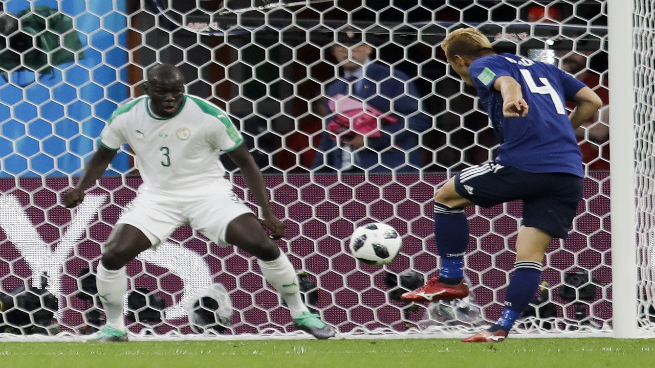 Japan's Keisuke Honda, right, scores his side's second goal past Senegal's Kalidou Koulibaly during the group H match at the 2018 football World Cup at the Yekaterinburg Arena in Yekaterinburg , Russia, Sunday, June 24, 2018. (AP Photo/Natacha Pisarenko).