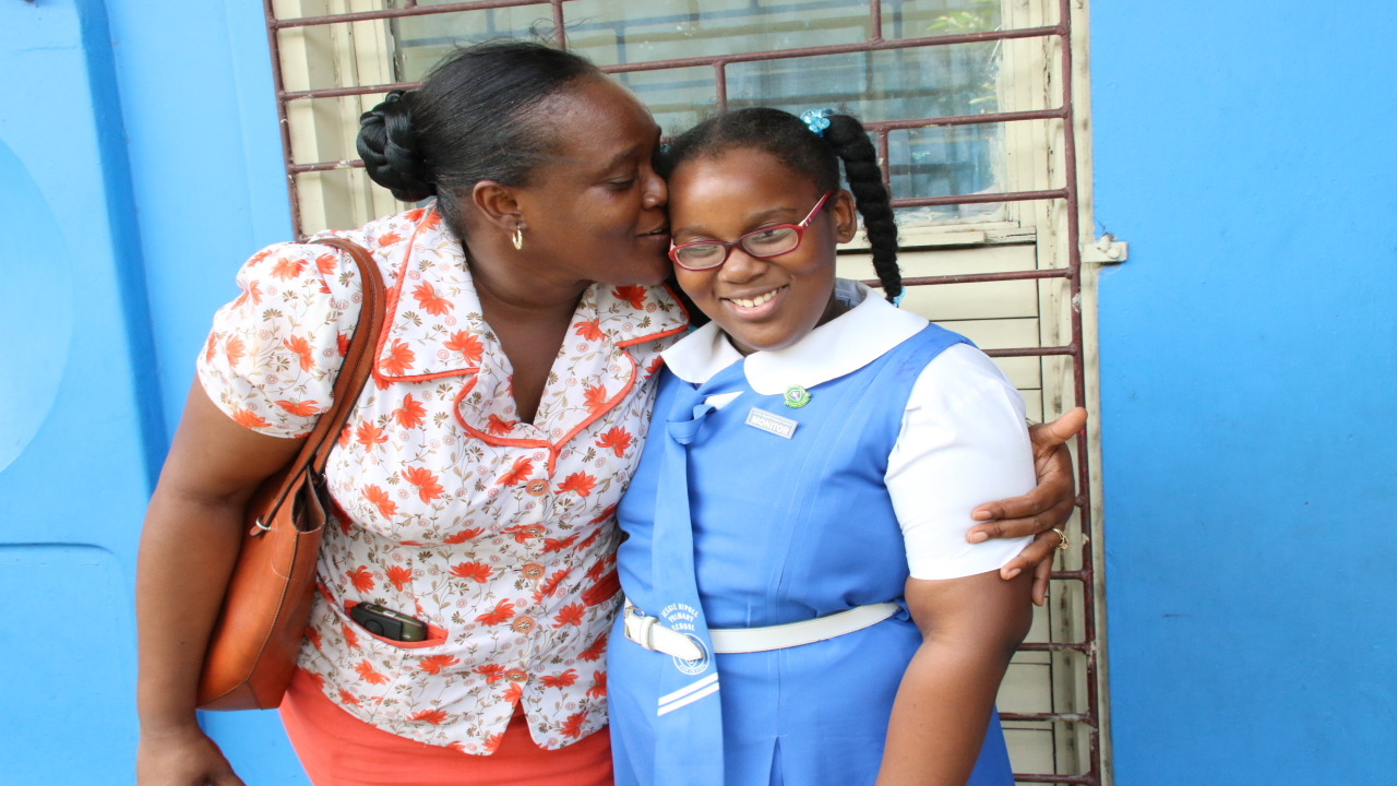 Jaxine Scott plants a kiss to the cheek of her daughter Jayda Irving after the release of GSAT results on Thursday. Jayda was placed at Wolmer's Girls' School. (PHOTOS: Llewellyn Wynter)