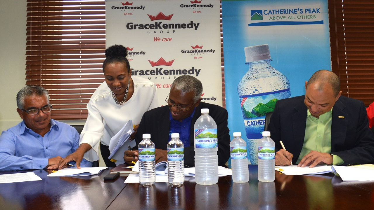 (L-R) David Wong, Managing Director of Peak Bottling Company Ltd; Shaun Lawson-Freeman, Legal Counsel – GraceKennedy ltd; Michael Bernard, Chairman of Peak Bottling and Don Wehby, Group CEO - GraceKennedy Ltd at the signing of a binding memorandum of understanding between the two companies held on Monday.