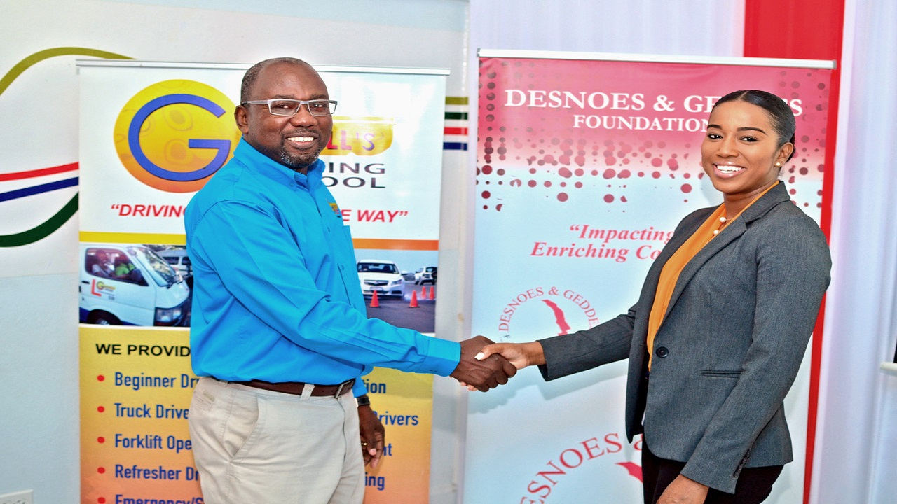 (L – R) Managing Director of Grennell's Driving School, Alfonso Grennel, welcomes Red Stripe's Communications and Sustainability Executive Tyheissa Williams, representing the Desnoes and Geddes (D&G) Foundation, as the title sponsor at the media launch of Staging of the Jamaica Driver and Traffic Safety Expo.