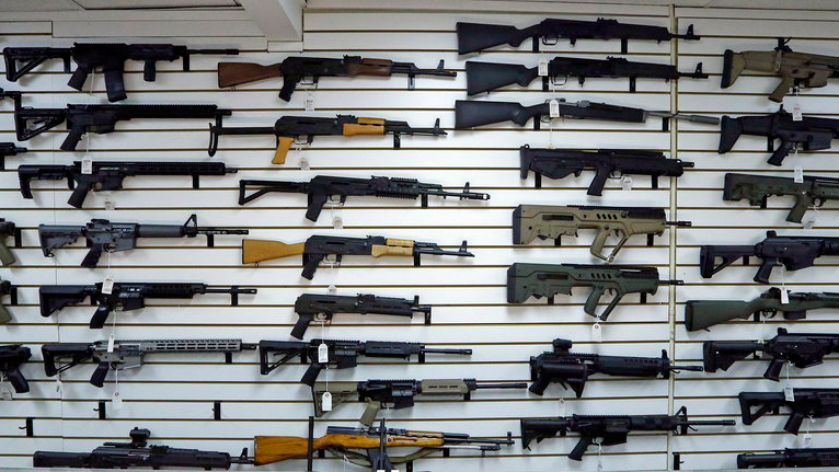 FILE - This Nov. 7, 2017, file photo shows dozens of semi-automatic rifles on a wall in a gun shop in Lynnwood, Wash. A new study by the Small Arms Survey released Monday, June 18, 2018, of small arms estimates there are over 1 billion legal and illicit firearms in the world today, including 857 million in civilian hands — with American men and women the dominant owners. (AP Photo/Elaine Thompson, File)