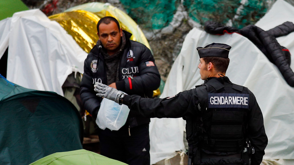 French gendarme gestures to a migrant as they are clearing out a makeshift migrant camp along side of the canal Saint Martin, in central Paris, France, Monday, June 4, 2018. French police have evacuated around 500 migrants, mostly Afghans but some Africans from a makeshift tent encampment. (AP Photo/Francois Mori)