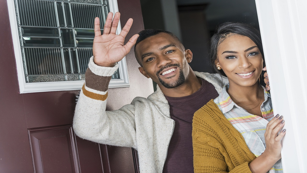 Stock image of a man and woman standing at the entrance to their home.