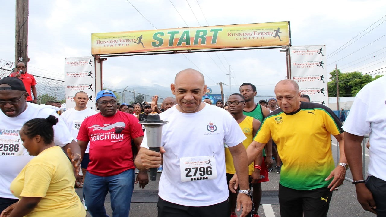 Commissioner of Police Major General Antony Anderson (centre) and others participate in the Torch Run on Saturday. (PHOTO: Llewellyn Wynter)