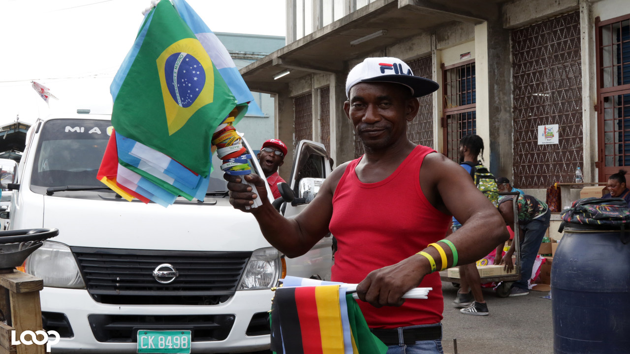 Downtown Kingston vendor Oswald Green displays his flags for sale on Tuesday evening ahead of the start of the World Cup. (PHOTOS: Ramon Lindsay)