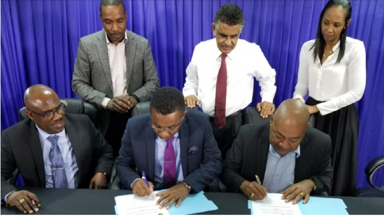 UHWI CEO Kevin Allen (centre) and JFF President Michael Ricketts (right) sign an MOU that will see the hospital offering a range of medical services to players in the national programme. JFF General Secretary Dalton Wint is at left.  Also witnessing the signing of the MOU are (from left standing)  Dr Carl Bruce, consultant neurosurgeon of the UWHI;  Dr Guyan Arscott, chairman of the JFF Medical Committee; and  Sophia Harris-Lau, JFF director of marketing and business development.