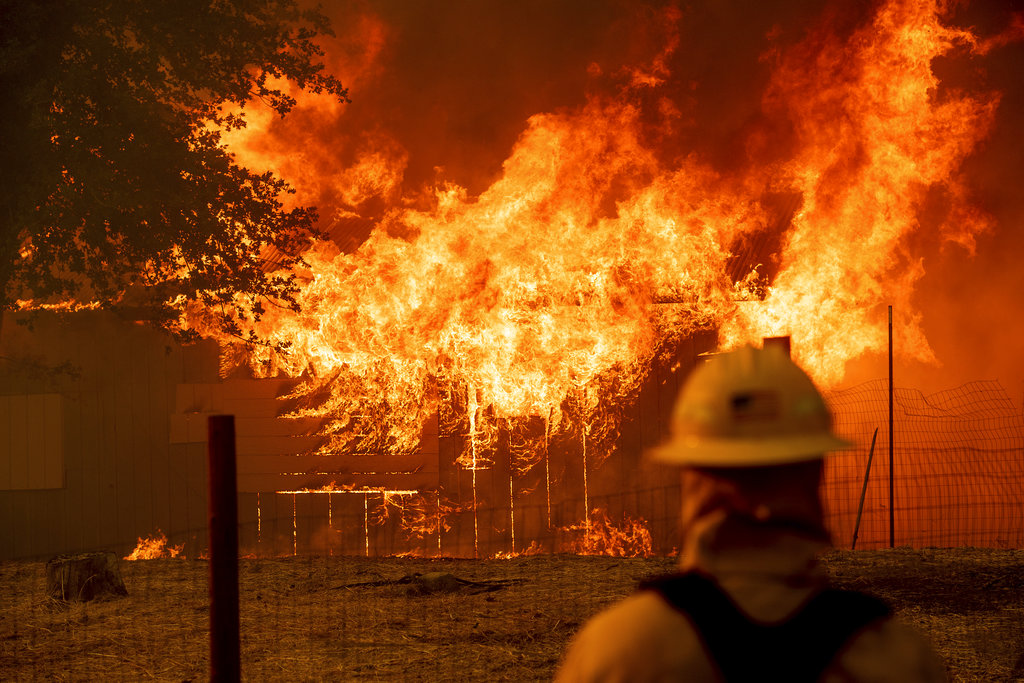 A firefighter monitors a burning outbuilding to ensure flames don't spread as the River Fire burns in Lakeport, Calif., on Monday, July 30, 2018. A pair of wildfires that prompted evacuation orders for nearly 20,000 people barreled Monday toward small lake towns in Northern California, and authorities faced questions about how quickly they warned residents about the wildfires. (AP Photo/Noah Berger)