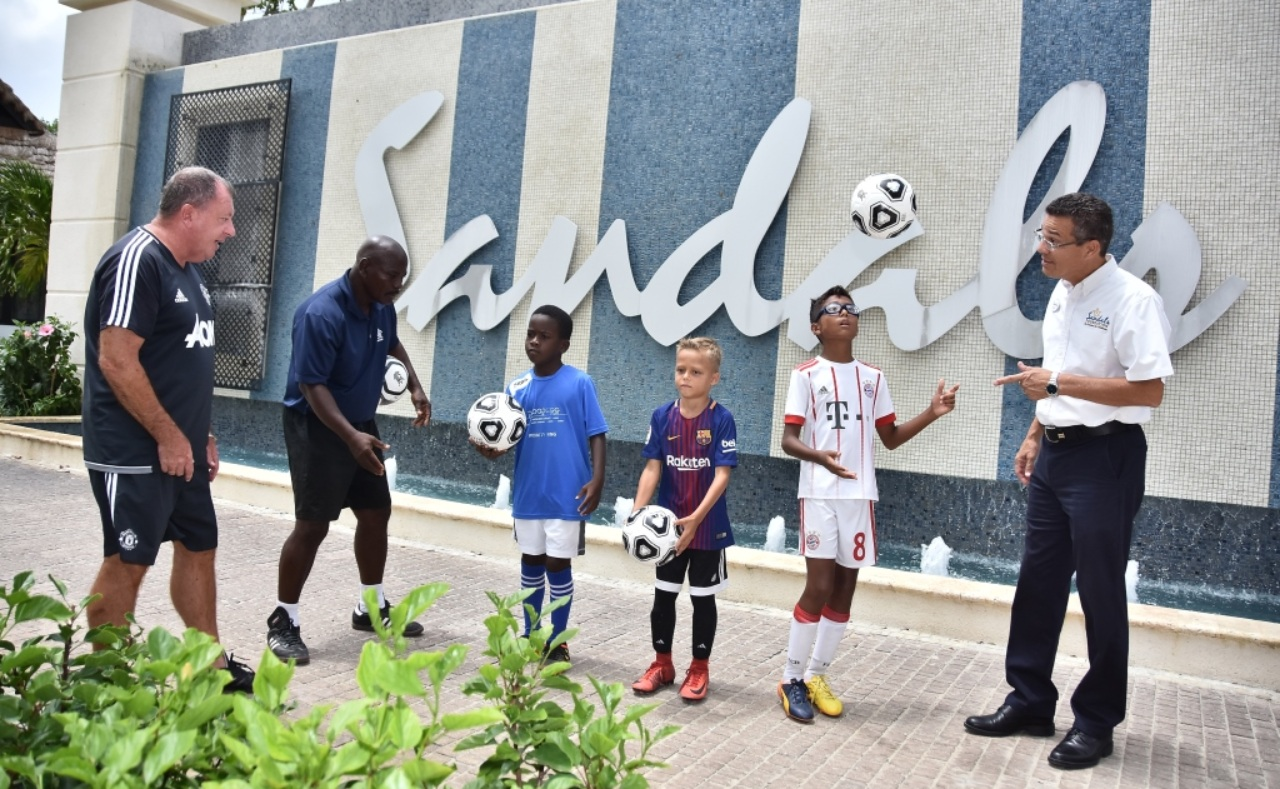 1.	(L-R) Manchester United Youth Academy Football Coach Louis Garvey watches on as Dexter Marshall asks some of his students to showcase their skills to Sandals Barbados General Manger Ferry Zievinger.