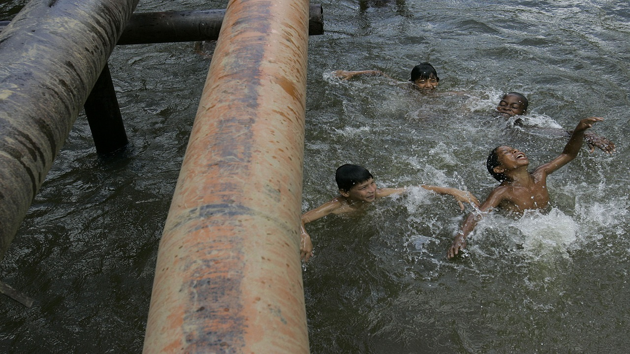 Children play under oil pipes that cross a river in the province of Sucumbios, Ecuador.