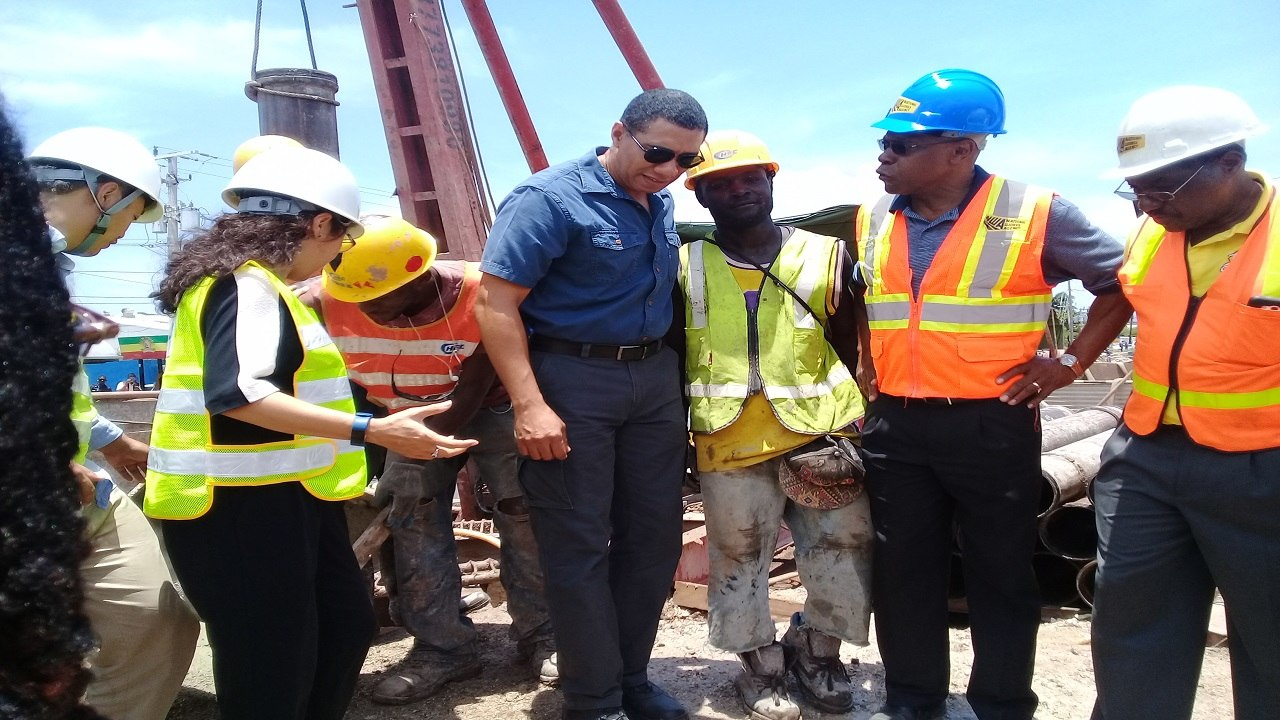 Prime Minister Andrew Holness (centre) listens to a point in discussion with National Works Agency CEO EG Hunter (second right) during a tour of the infrastructural projects across the Corporate Area recently.