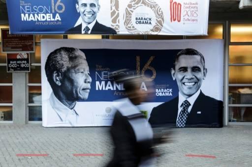 Les portraits de Nelson Mandela et de Barack Obama sur une affiche à l'entrée du stade Wanderers, le 17 juillet 2018 à Johannesburg, où l'ancien président américain prononcera un discours, point d'orgue des célébrations du centième anniversaire de la naissance du premier chef d'Etat noir sud-africain