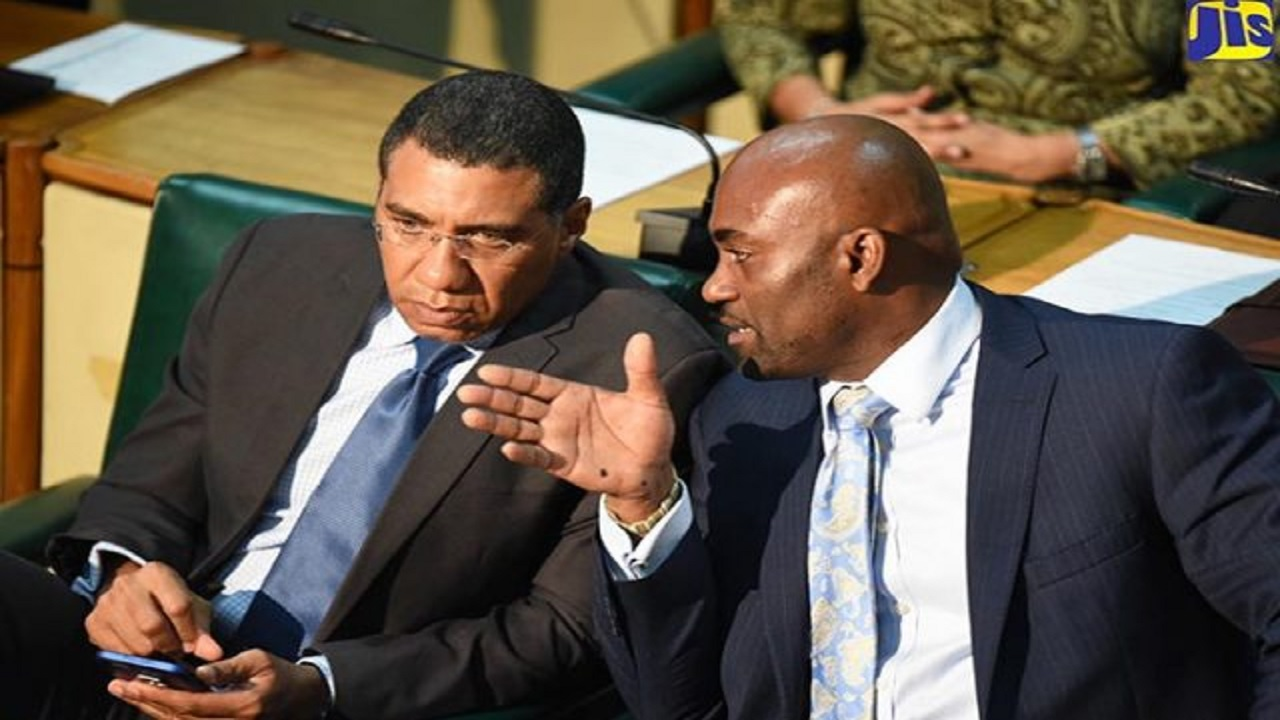 Prime Minister Andrew Holness (left), listens keenly to Science and Technology Minister, Dr Andrew Wheatley, during a recent sitting of the House of Representatives. (PHOTO: JIS)