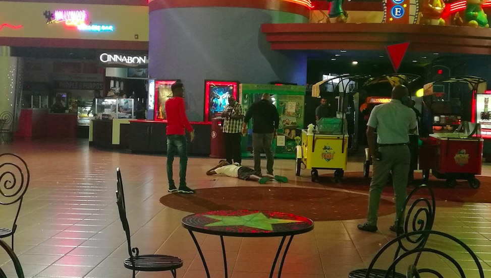 Security officials detain a suspect after a stabbing at MovieTowne Port of Spain