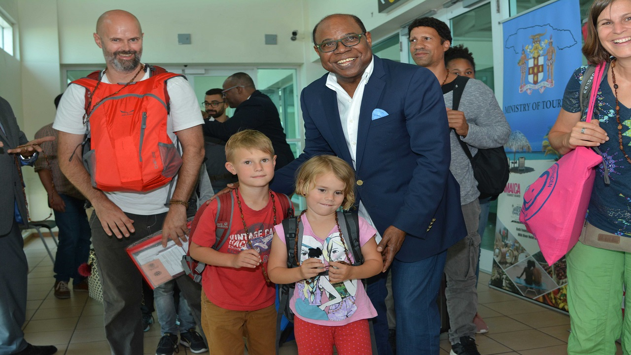 Tourism Minister Edmund Bartlett greets two young German tourists as they arrive in Jamaica following Eurowings' inaugural weekly scheduled flights between Munich and Montego Bay.