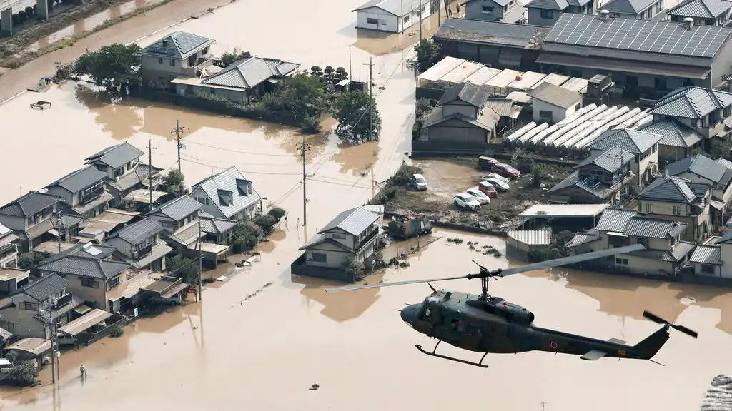 A helicopter flies over a flooded housing area in Kurashiki, Okayama prefecture, western Japan Monday, July 9, 2018. (Kyodo News via AP)