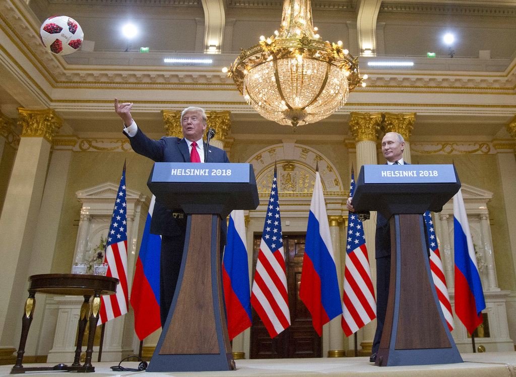 U.S. President Donald Trump, left, tosses a football to his wife first lady Melania Trump after Russian President Vladimir Putin presented it to him during a press conference after their meeting at the Presidential Palace in Helsinki, Finland, Monday, July 16, 2018. (AP Photo/Pablo Martinez Monsivais)