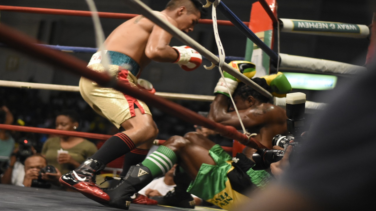 Canada's Ricardo 'Magic Man' Salas sends Jamaican Richard 'Frog' Holmes to the canvas in the second round of the 2018 Wray and Nephew Contender boxing final on Wednesday night at the National Indoor Sports Centre. (PHOTO: Marlon Reid).
