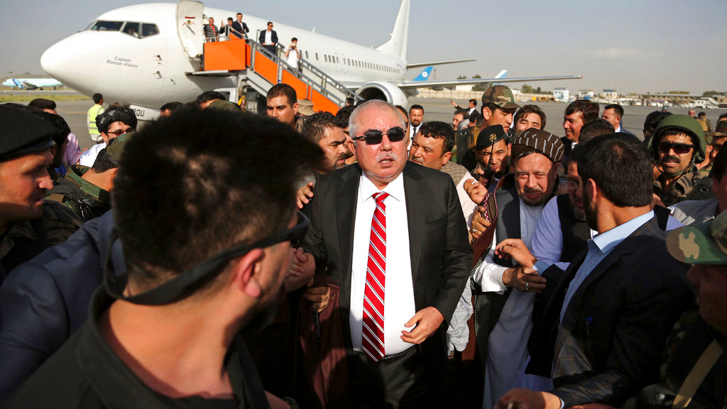 Afghan first vice president, a former Uzbek warlord, Gen. Abdul Rashid Dostum, center, and members of his entourage arrive at Kabul International Airport in Kabul, Afghanistan, Sunday, July 22, 2018. An Afghan spokesman said there has been a large explosion near the Kabul airport shortly after Dostum landed on his return from abroad. Dostum and his entourage were unharmed in the explosion which took place after his convoy had already left the airport. (AP Photo/Rahmat Gul)