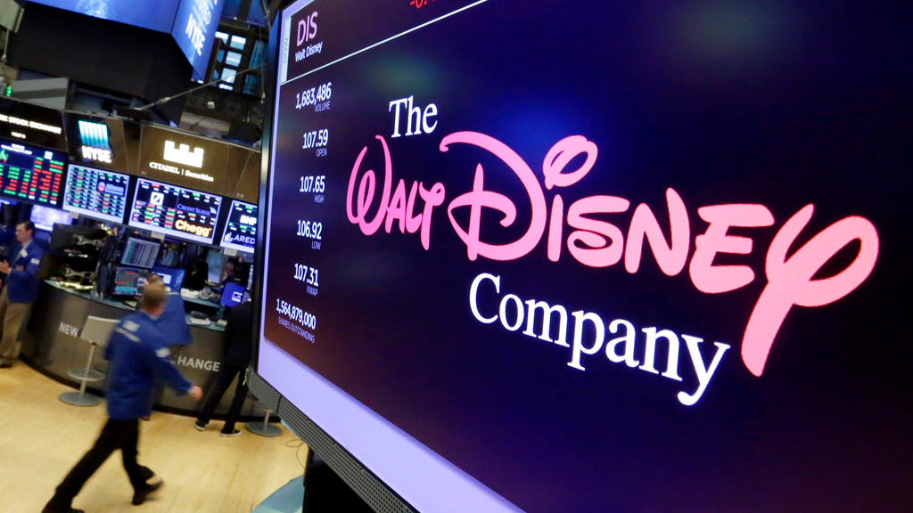 FILE - In this Aug. 8, 2017, file photo, The Walt Disney Co. logo appears on a screen above the floor of the New York Stock Exchange. Disney's $71.3 billion acquisition of Twenty-First Century Fox's entertainment division is one step closer after shareholders approves the deal Friday, July 27, 2018. The tie-up brings together Marvel's X-Men and Avengers franchises and creates an entertainment behemoth in the digital streaming era. (AP Photo/Richard Drew, File)