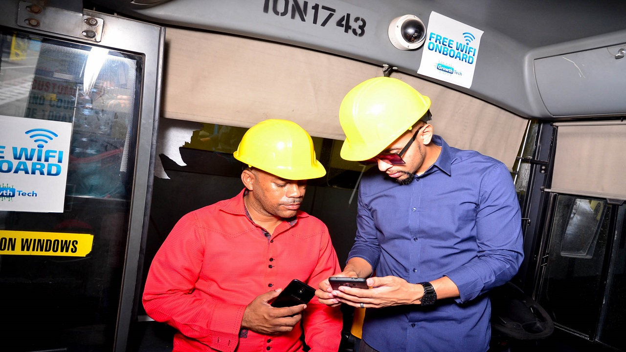 Growth Tech Ltd's CEO Neil Lawrence (right), demonstrates Wi-Fi log in to JUTC's Maintenance Manager Michael Kelly at the company's Ashenheim Road Depot