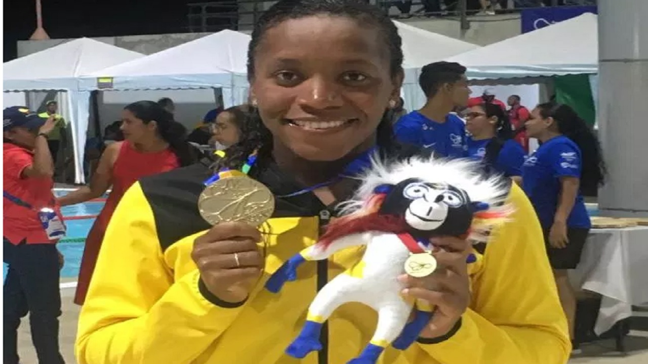 Alia Atkinson shows off one of her three gold medals at the CAC Games in Barranquilla, Colombia.