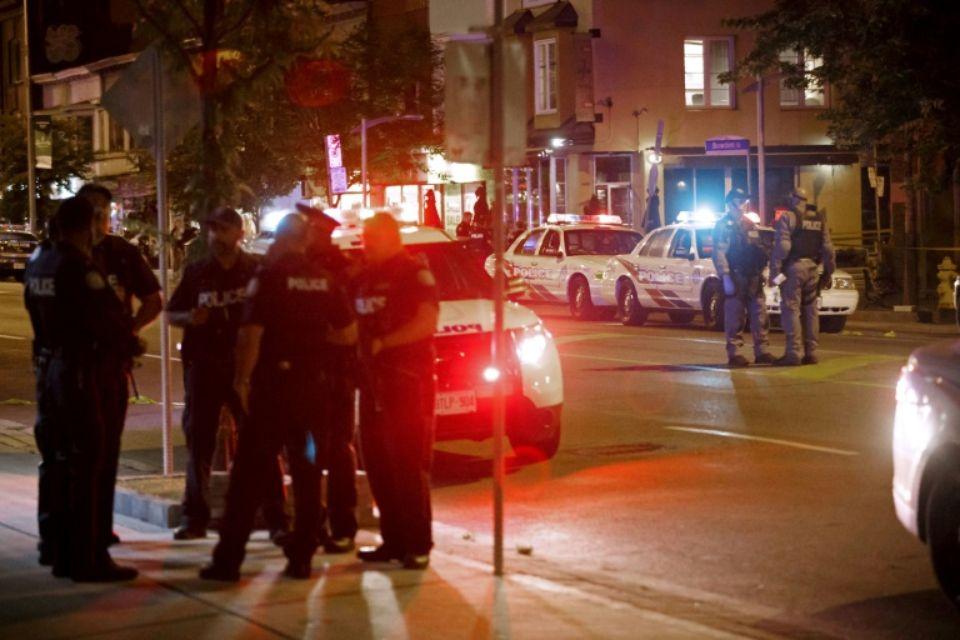 Des policiers de Toronto dans Danforth Street, sur la scène de la fusillade qui a fait deux morts, le 23 juillet 2018