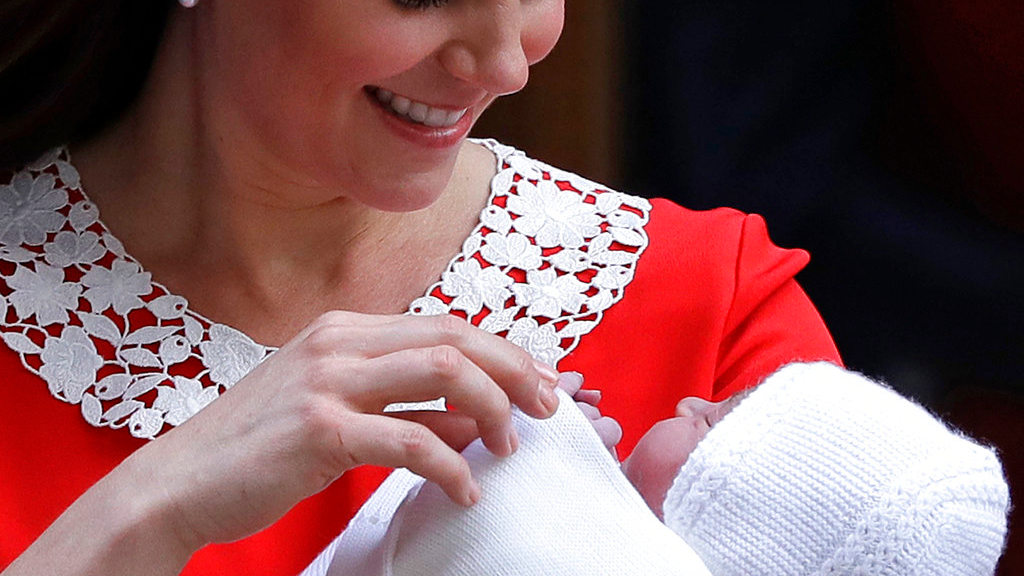 In this file photo dated Monday, April 23, 2018 Kate, Duchess of Cambridge holds her newborn baby son, to be named Prince Louis, as she leaves the Lindo wing at St Mary's Hospital in London London. The Christening of Prince Louis, third child of the Duke and Duchess of Cambridge, will take place Monday July 9, 2018, at Chapel Royal in St. James's Palace, London. (AP Photo/Kirsty Wigglesworth, FILE)