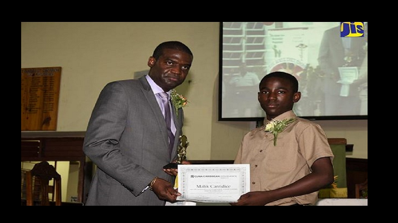 President of the Ackee Tree Group, Hopeton Brandford (left), presents a scholarship to Malik Carridice of Porus Primary School in Manchester on Saturday, July 7 at Trinity Baptist Church in Porus, Manchester. Photo: JIS.
