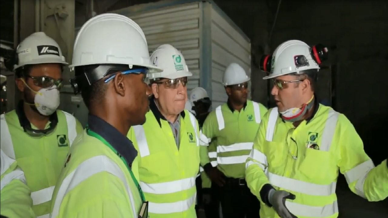 Minister of Industry, Commerce, Agriculture and Fisheries Audley Shaw (centre) listens as General Manager of Carib Cement, Peter Donkersloot (right) shares details of the company's plans. Other employees listen on.