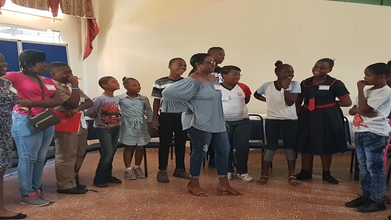 Dr. Patrece Charles, counselling psychologist of the Phoenix Counselling Centre, has the rapt attention of the children attendees at the recent workshop on transitioning from primary to high school held at the Rex Nettleford Multi-Purpose Hall.