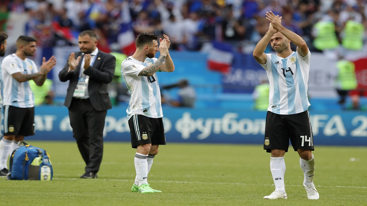 Argentina's Lionel Messi, center, and Argentina's Javier Mascherano, right, acknowledge the fans at the end of the round of 16 match against France, at the 2018 football World Cup at the Kazan Arena in Kazan, Russia, Saturday, June 30, 2018. (AP Photo/Ricardo Mazalan).